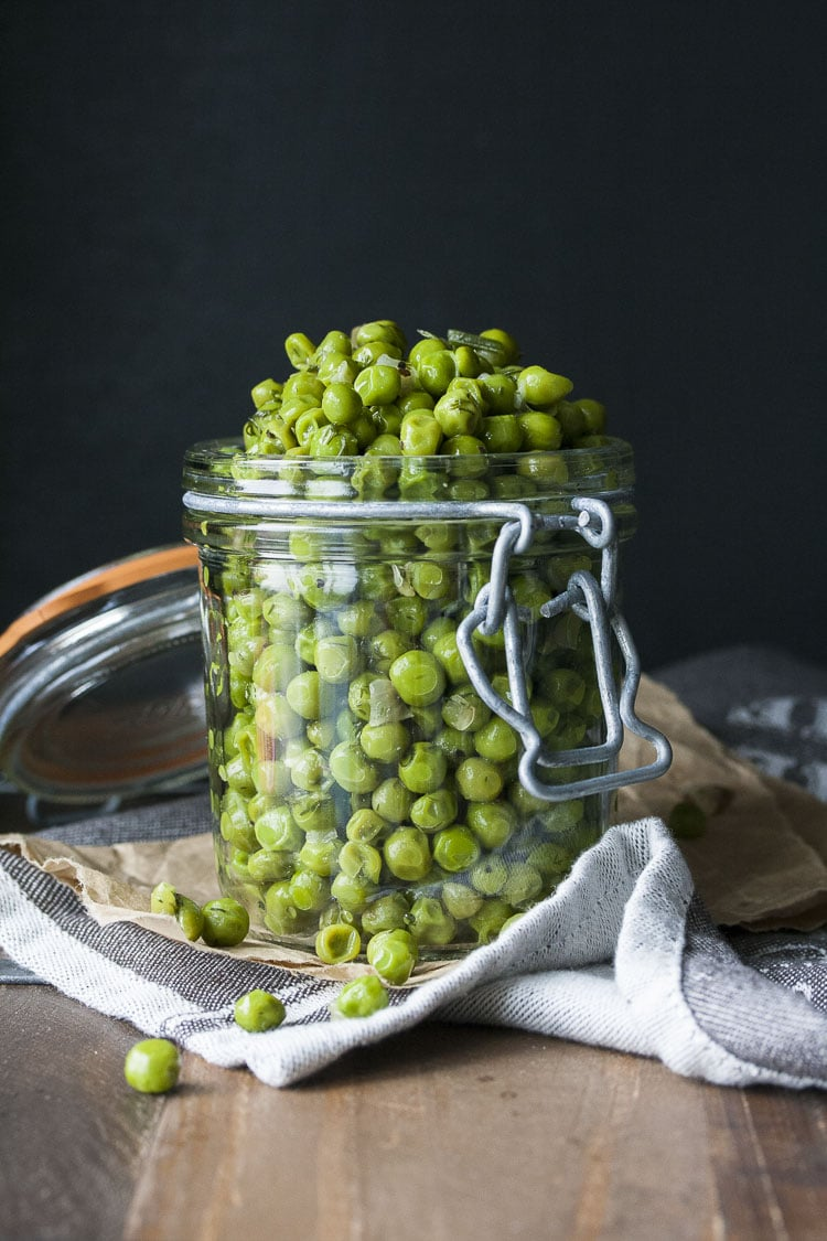 Cooked peas with scallions and dill piled high in a glass jar