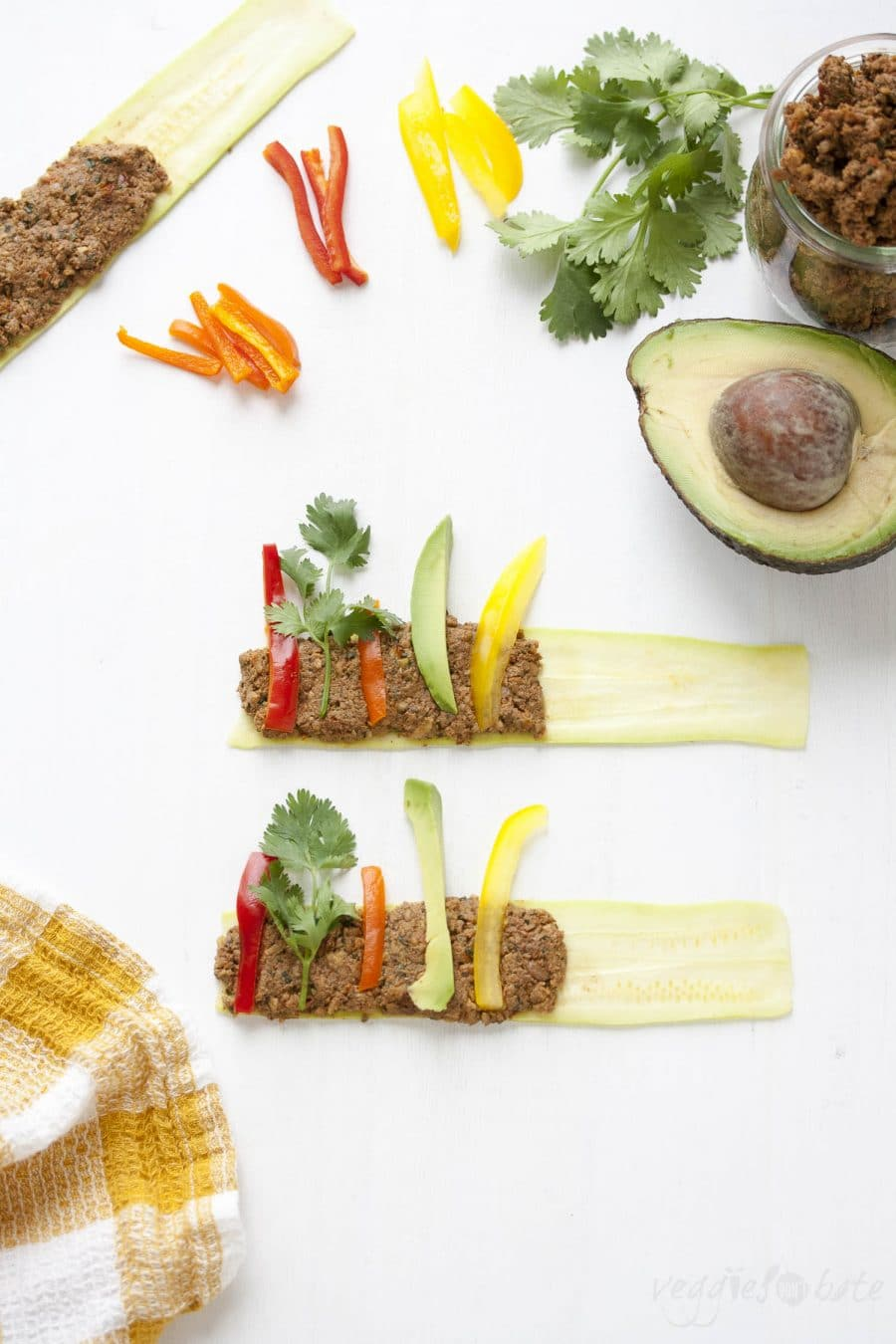 """Sliced zucchini covered with raw walnut """"meat"""" and raw veggie slices"""